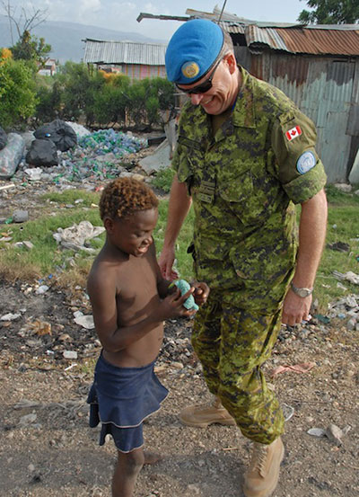 Lieutenant Commander Ian Cook, Chief of Staff coordinator for the mission MINUSTAH, speaks to a child that lives beside this main garbage depot in Port-Au-Prince. Many Haitian families live in this unsanitary environment. June 23, 2008 in Port-Au-Prince, Haiti. Photo by Sgt Robert Comeau Army News, Combat Camera.