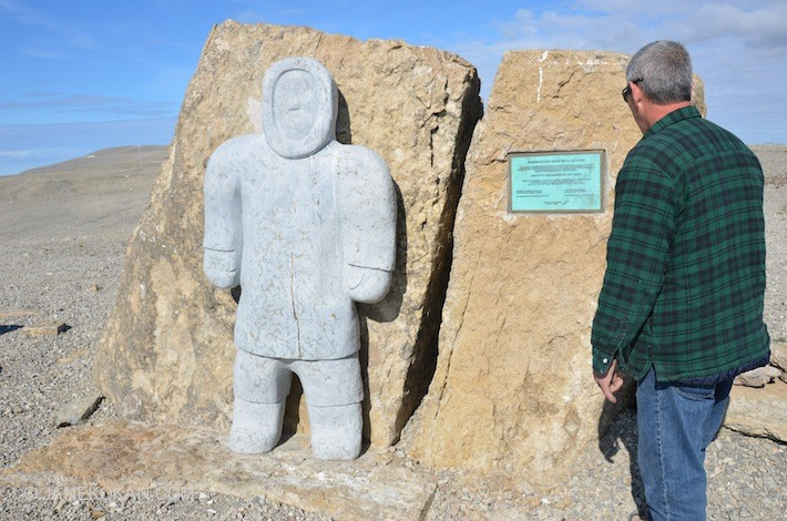 Man looking at Arctic Exiles monument 1